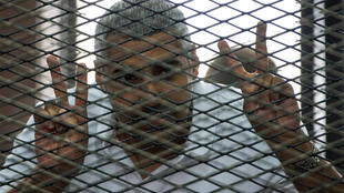 Mohamed Fahmy listens to the verdict inside the defendant's cage at his trial on 23 June 2014.