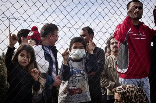 Migrants and children stand behind a fence at the Hellinikon camp in Athens, on February 6, 2017, in a protest at poor living conditions, during a visit of the Greek Immigration Minister.