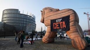 Protestors stand in front of a Trojan Horse balloon with a banner reading 'Stop Ceta' as they demonstrate against the Transatlantic Trade and Investment Partnership (TTIP) and EU-Canada CETA agreement in front of the Euroean parliament building.