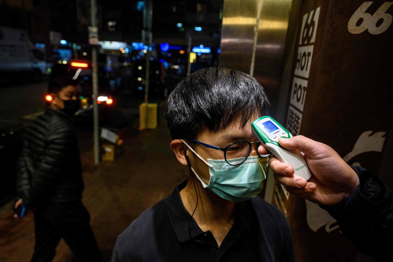 Sur cette photo prise le 11 février 2020, un membre du personnel d'un restaurant se fait prendre la température, dans le quartier animé de Mongkok à Hong Kong.
