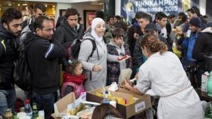 Des bénévoles distribuent boissons et nourritures à des réfugiés arrivant à la gare suédoise de Malmo, le 10 septembre 2015.