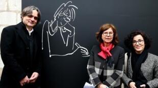 Véronique Cabut, veuve du dessinateur français Cabu, pose aux côtés de Riss et Coco, lors d'une exposition en son honneur, en Châlons-en-Champagne, le 1er décembre 2018.