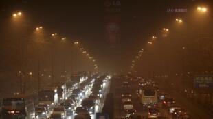 Des voitures sur une avenue de Pékin, lors d'une soirée brumeuse, le 29 janvier 2013