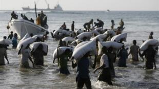 Des hommes déchargent des sacs de céréales fournis par le Programme alimentaire mondial, le 5 décembre 2007.