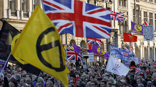 Protesters hold up placards and Union flags as they attend a pro-Brexit rally promoted by UKIP (United Kingdom Independence Party) in central London on December 9, 2018.