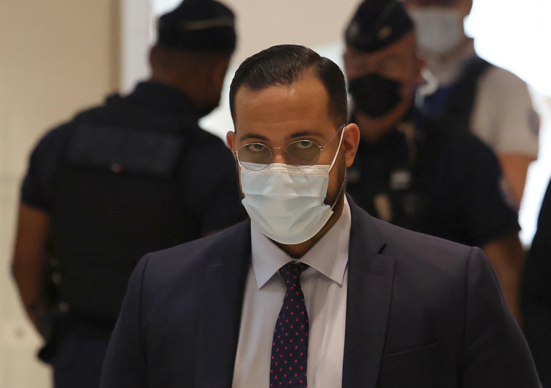 Alexandre Benalla (C), con una máscarilla, un ex guardaespaldas del presidente francés, llega para ser juzgado en París, el 13 de septiembre de 2021, acusado de agresión durante una protesta del 1° de Mayo de 2018.