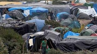 "Migrants walk near tents in the ""New Jungle"" makeshift camp in Calais, northern France"