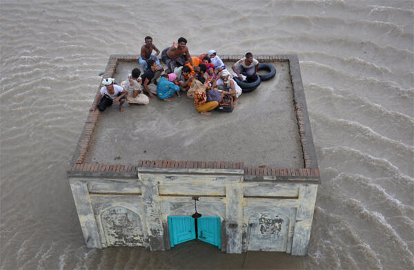 A family takes refuge on top of a mosque while awaiting rescue from flood waters in Sanawa, Punjab province
