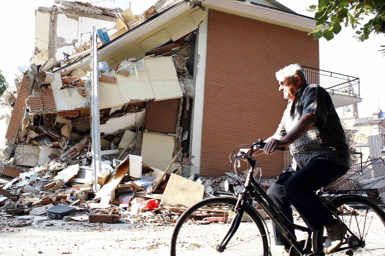 Italiano passa em frente à construção totalmente destruída pelo terremoto que matou 16 pessoas e feriu outras 350, em Cavezzo, em foto desta quarta-feira.