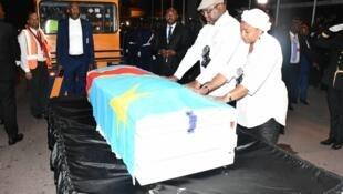 Le président congolais Félix Tshisekedi devant le cercueil de son père à l'aéroport de Kinshasa, aux côtés de la première dame.