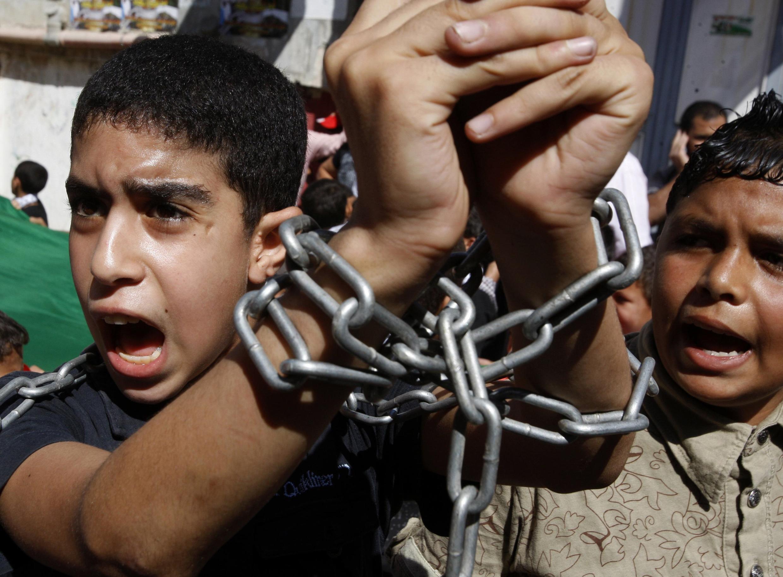 Một thiếu niên Palestine tự trói hai tay, tham gia vào một cuộc biểu tình đòi trả tự do cho các tù nhân Palestaine tại Israël, 14//102011, tại một trại tị nạn vùng Cisjordanie.