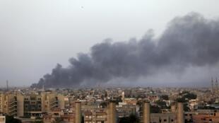 De la fumée s'élève au dessus de la zone des combats entre milices islamistes et troupes du général Khalifa Haftar, non loin de l'aéroport de Benghazi, en Libye, le 23 août 2014.
