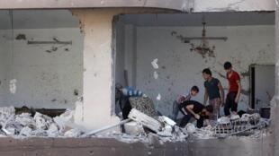 Des Syriens cherchent leurs affaires dans les décombres de leur immeuble, le 7 août 2013, dans la province de Ragga, à l'est.