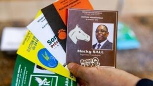 Un électeur sénégalais montre les différents bulletins de vote pour les cinq candidats à la présidentielle sénégalaise, le 24 février 2019 à Dakar.