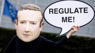 """Un activista de la ONG ambientalista Avaaz con una máscara que representa al CEO de Facebook, Mark Zuckerberg, sostiene un cartel que dice """"Regúlame"""" durante una acción que marca el lanzamiento de la Ley de Servicios Digitales, frente al edificio de la Comisión Europea, en Bruselas, el 15 de diciembre de 2020."""