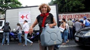Mulher carrega itens provenientes da primeira remessa de ajuda humanitária em Caracas, em 16 de abril de2019.