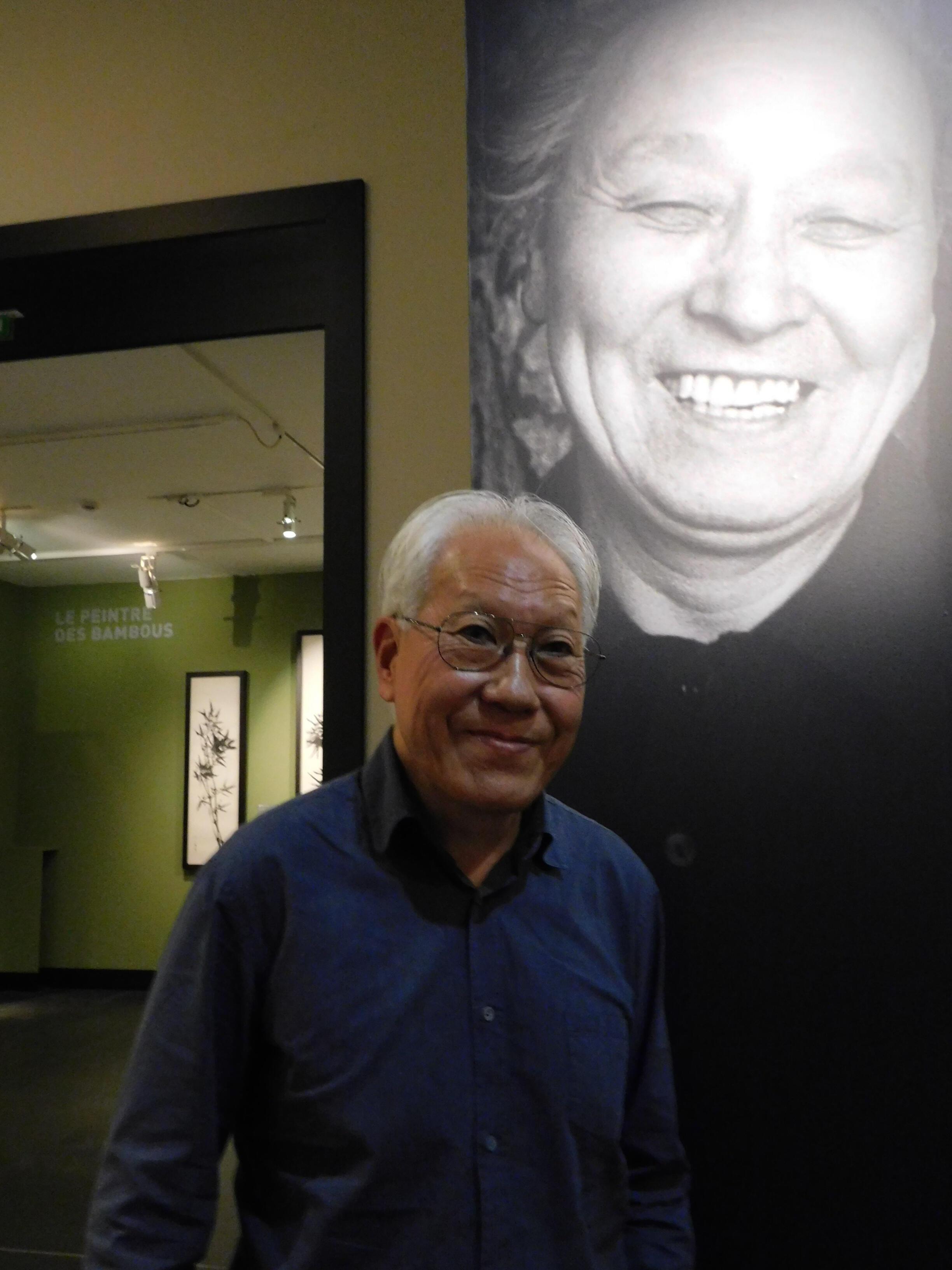 Le peintre Young-Sé Lee, sous le portrait de son père Lee Ungno au Musée Cernuschi.
