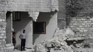 Homem observa estragos de bombardeios em sua casa, em Aleppo.