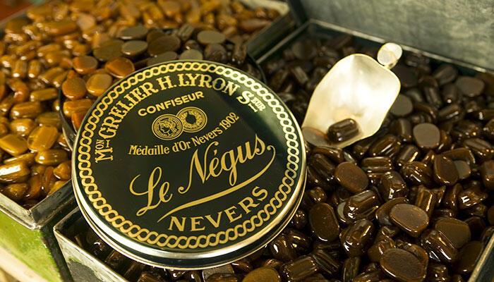 En l'honneur de l'empereur Ménélik d'Abyssinie, autrement nommé le Négus,un caramel mou au chocolat incrusté dans une carapace de caramel dur et brillant.