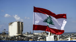 A Lebanese flag flies on a bridge near the port of Lebanon's capital Beirut, amid the destruction of Tuesday's explosion that killed over 150