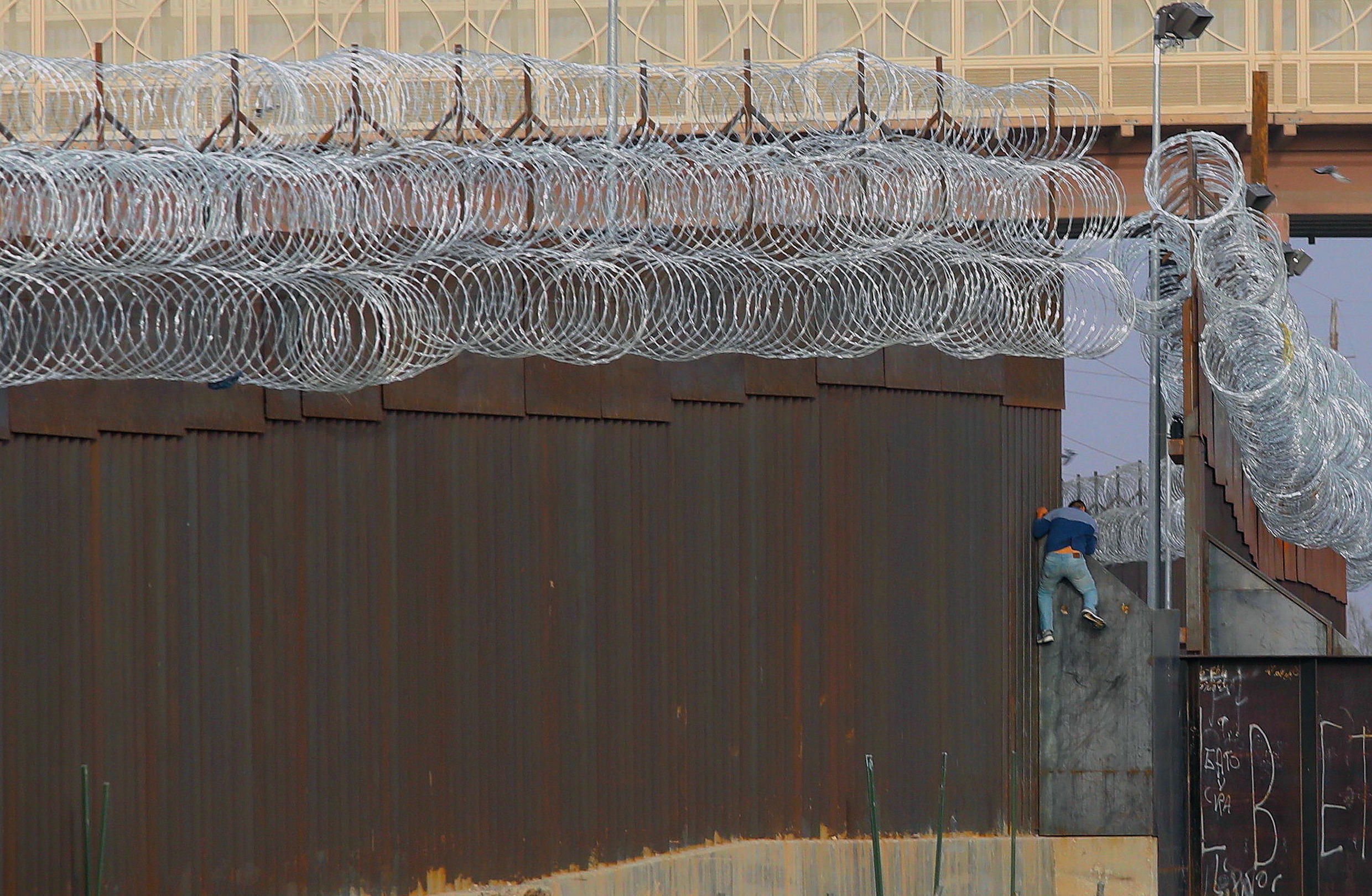 A migrant climbs the border fence in an attempt to enter the United States from the Mexican city of Ciudad Juarez