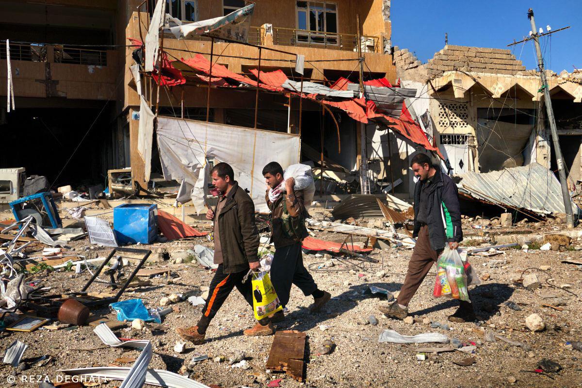Trois habitants de Sinjar traversent l'une des rues centrales de la ville, bombardée lors de l'offensive des forces armées kurdes irakiennes, vendredi 13 novembre 2015, pour libérer la ville détenue depuis août 2014 par le groupe Etat Islamique (Daech.)