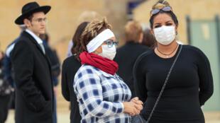 Mulheres israelitas protegidas com máscaras visitam o Muro Ocidental,um dos lugares mais sagrados do judaísmo.