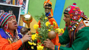 Shamans, holding apparel with the colours of the Netherlands soccer team, perform a good luck ritual in Lima