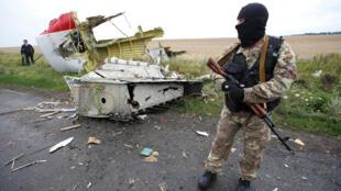 """No dia seguinte ao acidente, um rebelde pró-russo """"protege"""" os destroços do avião da Malaysia Airlines derrubado no leste da Ucrânia."""