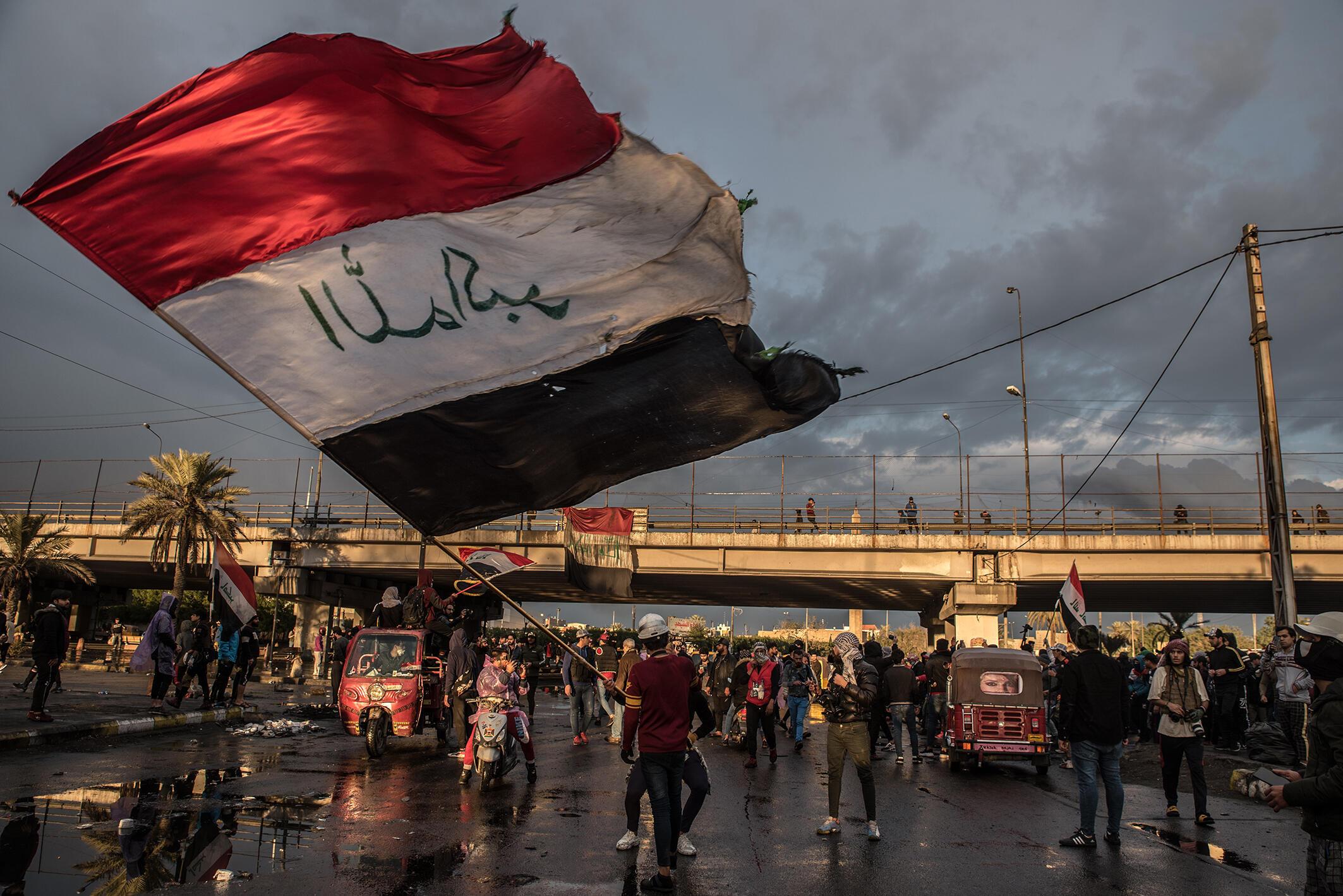 Un homme agite le drapeau irakien lors d'un cortège funèbre symbolique pour un manifestant tué la veille dans des affrontements avec les forces de sécurité. Bagdad, 21 janvier 2020.