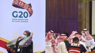 Una mujer pasa delante de un cartel de la cumbre del G20 nations en Riad, la capital saudita, el 18 de noviembre de 2020
