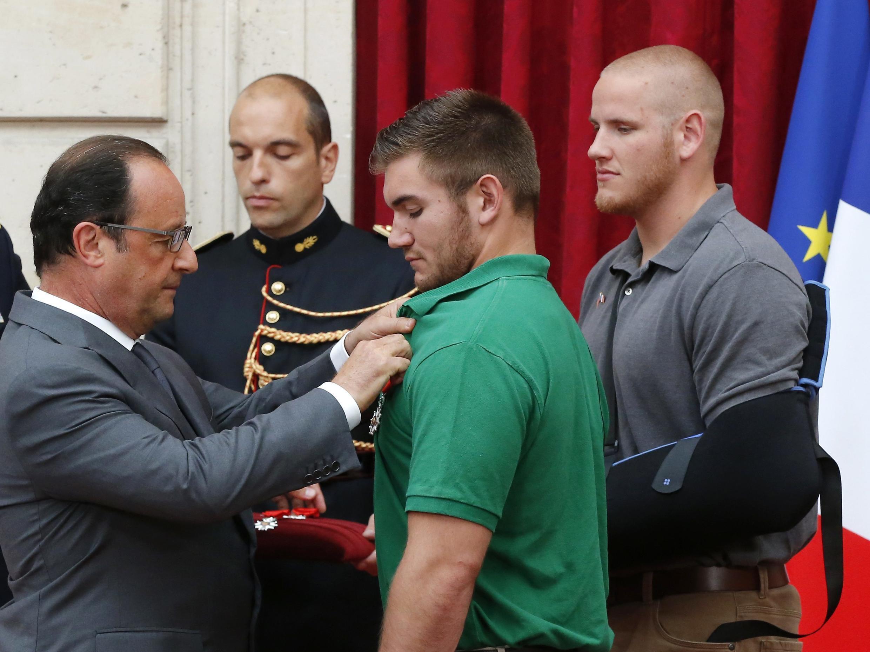 O presidente francês François Hollande condecora os militares americanos Alek Skarlatos (centro) e Spencer Stone (fundo), no Palácio do Eliseu, em 24 de agosto de 2015.