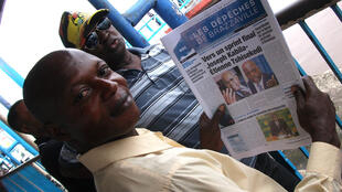 "Man reading Brazzaville newspaper with headline, ""Final sprint - Joseph Kabila & Etienne Tskisekedi"""