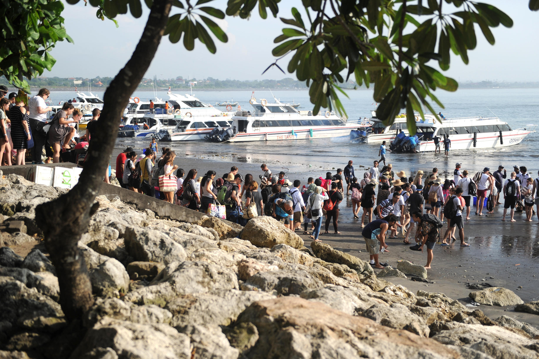 Les touristes se préparent à embarquer des bateaux pour l'île Nusa Penida de la plage de Sanur à Bali le 21 mars 2018.
