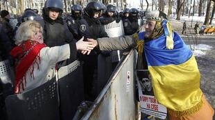 烏克蘭反政府與親政府示威民眾在警察面前握手,2014年2月6日。
