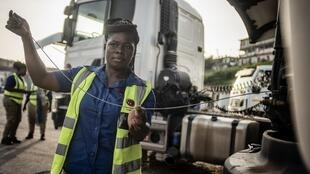 A female truck drivers checks her truck's oil level before the start of the workday in Takoradi, western Ghana, on April 3, 2019