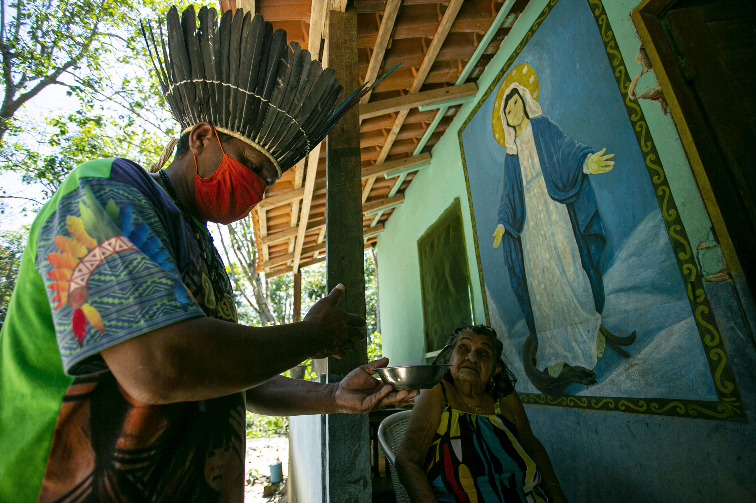 Chief Leno of the Kunaruara tribe delivers a natural medicine to a resident at his village beside the Tapajos River of the Santarem municipality in western Para state, Brazil, July 10, 2020.