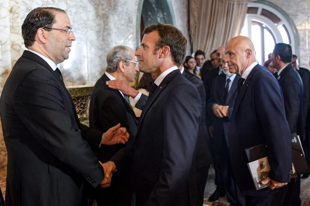 Emmanuel Macron (R) greets Tunisia's prime minister Youssef Chahed (L) at the state funeral of late Tunisian president Beji Caid Essebsi, 27 July 2019