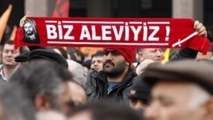 Lors d'un rassemblement à Ankara, un manifestant brandit une banderole sur laquelle on lit : <i>« Nous sommes Alevis ». </i>(2012)
