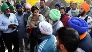 La cineasta india Jassi Sangha (c) conversa con los agricultores que protestan contra las reformas agrícolas  en Kundli, cerca de Nueva Delhi, India, el 29 de diciembre de 2020
