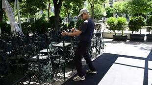 Un employé prépare la terrasse d'un restaurant de Madrid en vue d'une réouverture à partir du lundi 25 mai.