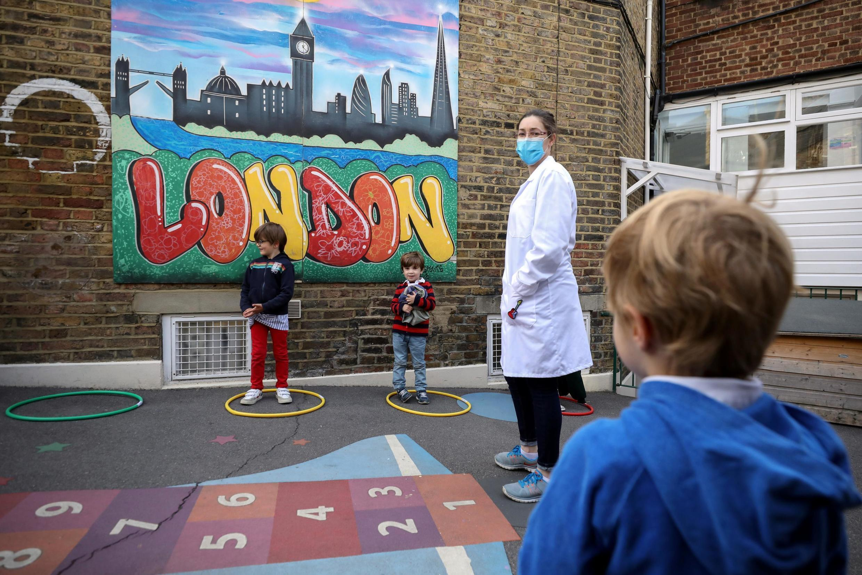 Des enfants utilisent des cerceaux dans une école de Fulham pour favoriser la distanciation sociale, au Royaume-Uni, pays le plus touché d'Europe, le 9 juin 2020.