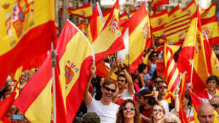 People wave Spanish and Catalan flags as they attend a pro-union demonstration organised by the Catalan Civil Society organisation in Barcelona, Spain, October 8, 2017.