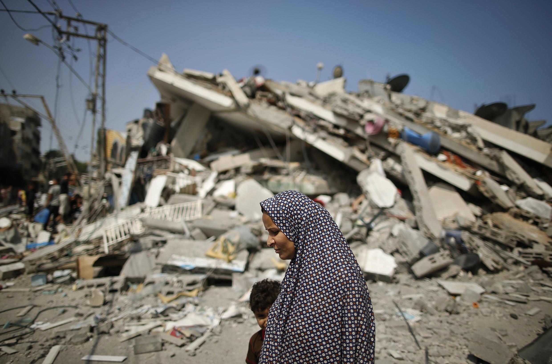 Palestina caminha com o filho entre as ruínas de Gaza nesta terça-feira
