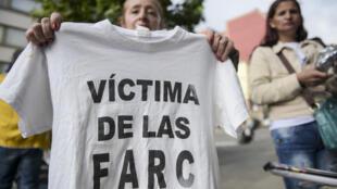 Une femme porte un t-shirt portant l'inscription «Victime des FARC» lors d'une manifestation à l'extérieur du siège de la Juridiction spéciale pour la paix (JEP) à Bogota le 13 juillet 2018.