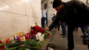 Un homme dépose une bougie sur un autel, à la mémoire des victimes de l'attentat du métro de Saint-Pétersbourg, le 4 avril 2017.