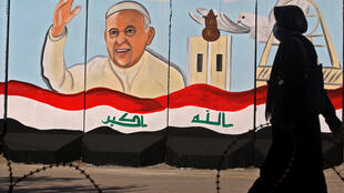 An Iraqi woman walks by a mural depicting Pope Francis on the outer walls of Our Lady of Salvation Church in Baghdad