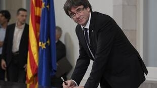 Catalan regional government president Carles Puigdemont signs a document about independence on 10 October