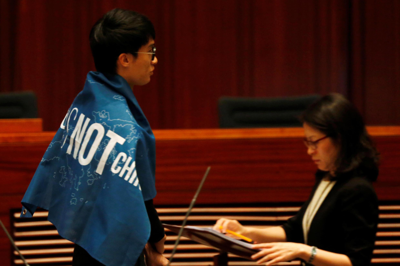 """2016年10月12日香港新一届立法会宣誓会议上,新当选议员梁颂恒身披写着""""香港不是中国""""的横幅。"""