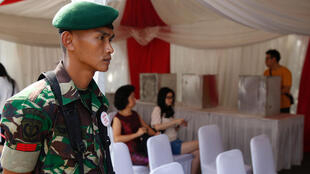 Un soldat en faction assure la sécurité d'un bureau de vote le 19 avril 2017 à Jakarta.